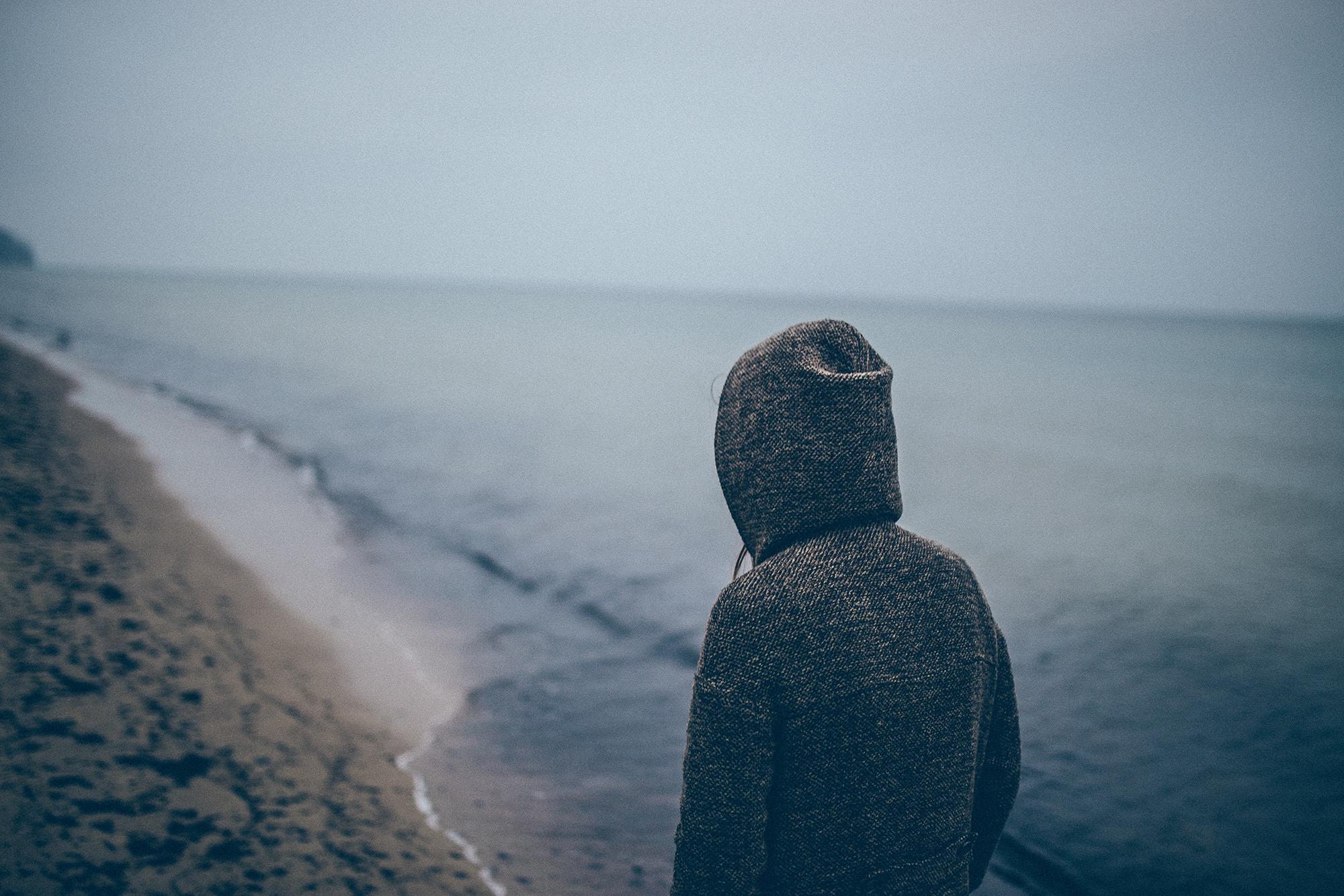 homem sozinho olhando para o mar do alto de uma montanha