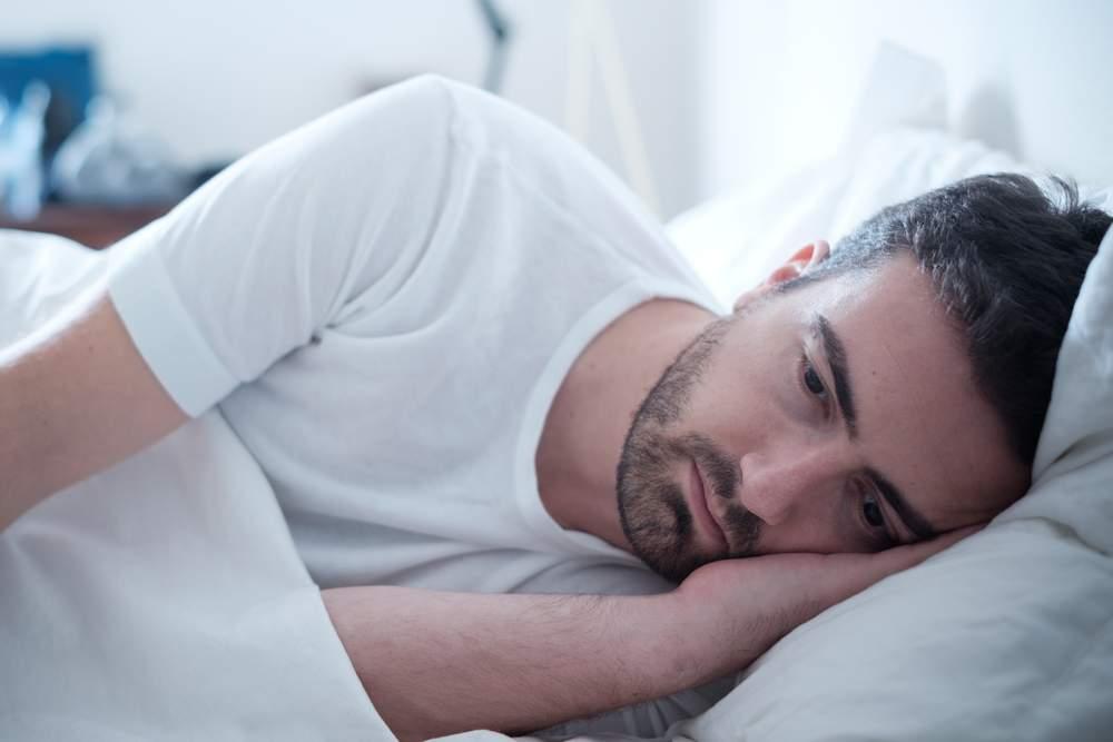 homem deitado na cama triste