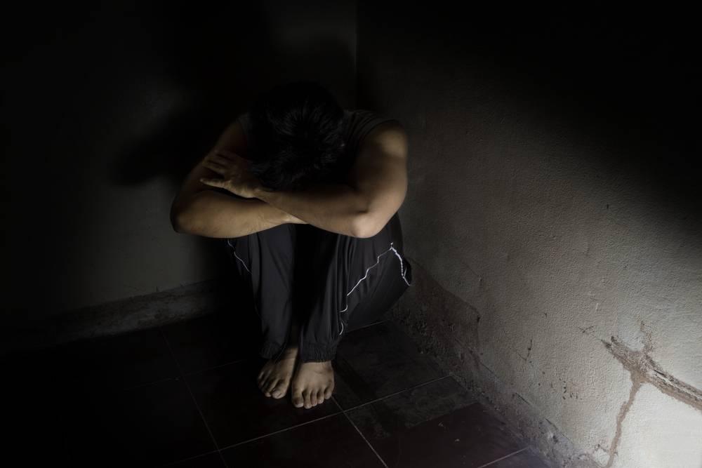 homem no canto da parede em um local escuro e com a cabeça entre as pernas