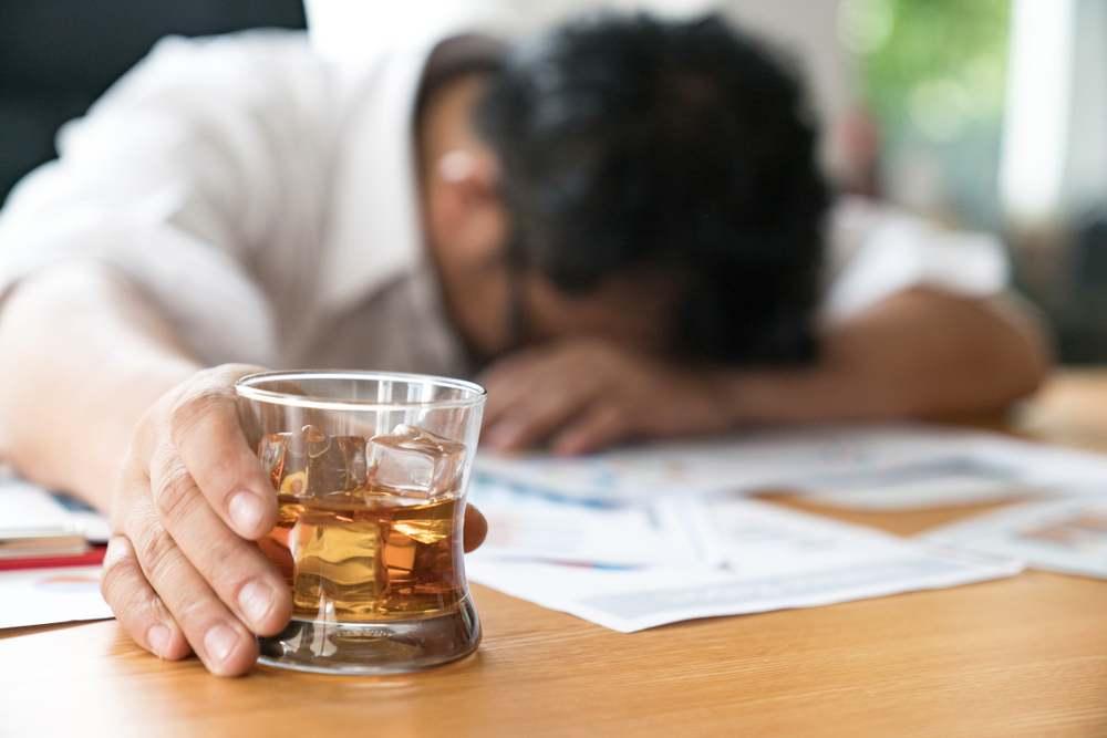 homem com a cabeça na mesa e o copo