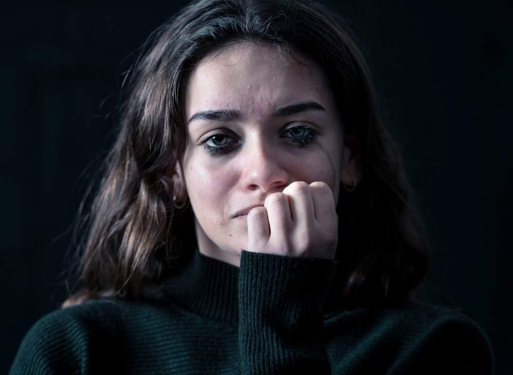 mulher com maquiagem borrada como se estivesse chorando