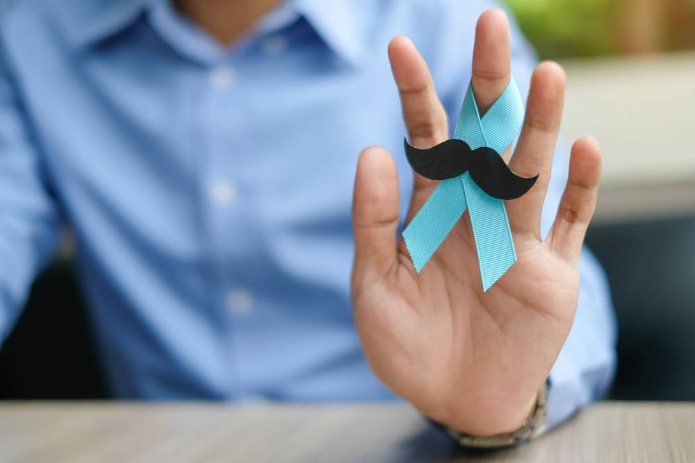 homem com o simbolo do novembro azul com um bigode no dedo do meio